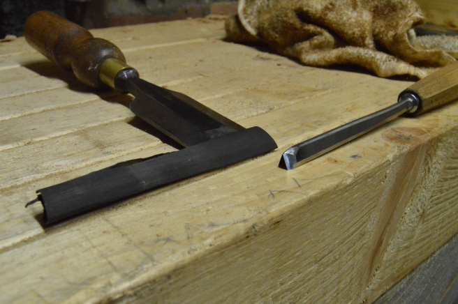The fine sandpaper folded over a wide chisel allows me to hone the inside angle